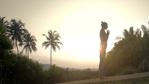 young yoga practitioner silhouette stands in namaste mudra pose on empty morning track at bright sunrise light low angle shot slow motion. Concept meditation and spiritual practices