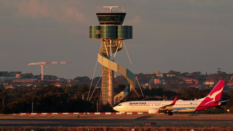 Sydney, Australia - May 31, 2019:  Qantas Boeing 737 taxis in front of the Control tower at Sydney airport with a Singapore airlines Boeing 777.