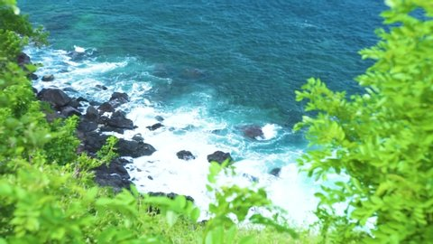 Sea waves splashing to rocky beach on green plant background. Rough ocean waves breaking to stony cliff with foam and spray while storm. Turquoise water crushing rocky cliff landscape