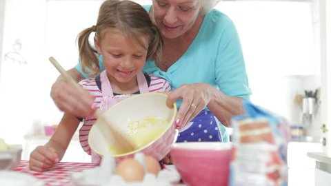 Grandmother mixes ingredients in bowl as granddaughter puts finger in and has a taste.Shot on Canon 5D Mk2 at at a frame rate of 25 fps