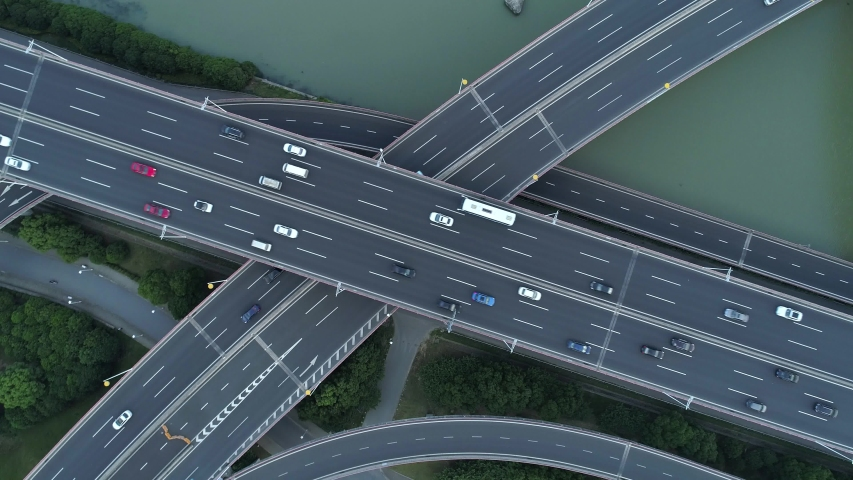 Aerial drone view of highway multi-level junction road with moving cars at sunset. Cars are moving on a multi-level road junction The concept of the urban. Suzhou city, China.