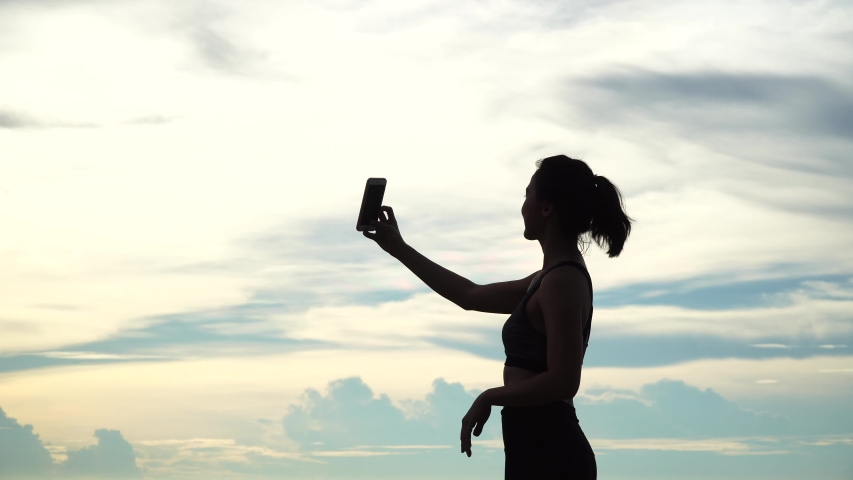 Silhouette of women have video chat using an smartphone, sharing a natural view with friends in social media. Fun and happy with nature #1031991794