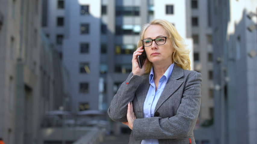 Senior female boss feeling angry and disappointed talking on phone, failure | Shutterstock HD Video #1032111464