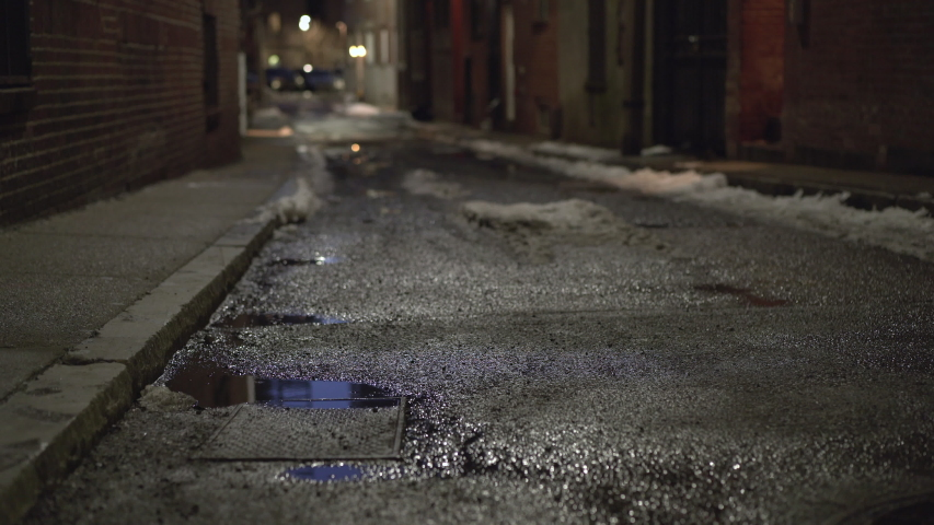 Dark side street of large city with puddle of water 4k