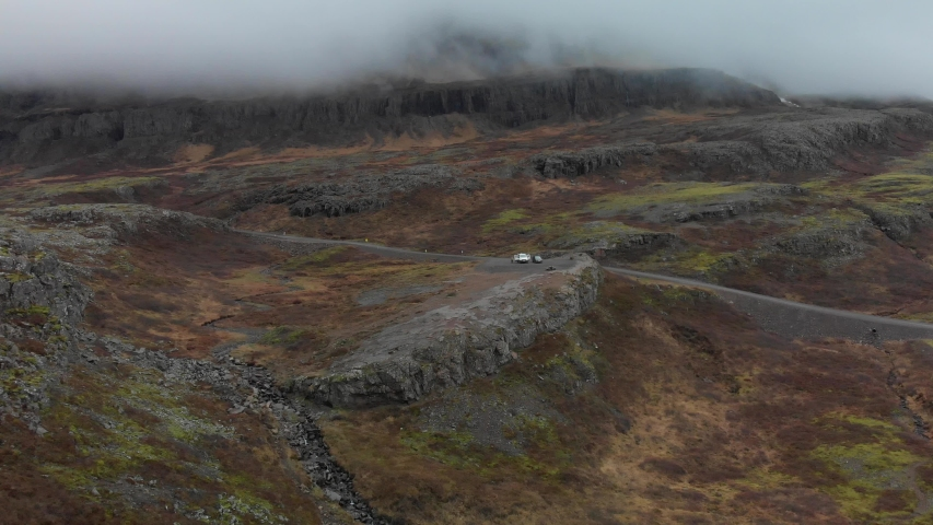 Flying in over a campervan and a car that is parked on top of a cliff in majestic landscape in Iceland, with massive mountains in the background, covered by a layer of thick fog and mist | Shutterstock HD Video #1032249434