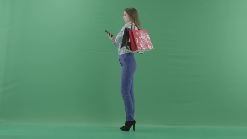 Woman with her purchases is talking on her mobile phone. Lady with straight brunette hair is wearing casual shirt and jeans. Female shopper holding shopping bags is standing on green background in a #1032282674