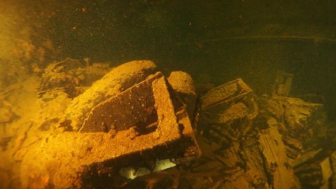 Sunken ship inside view on wreck underwater in Truk Lagoon on Chuuk Islands. Shipwreck in historic place of terrible tragedy of WW II and diver among wreckage of ship.