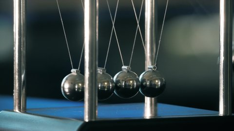 Newton's cradle in motion, five-ball system in one-ball swing. Close up shot with subtle color changing blurred background.