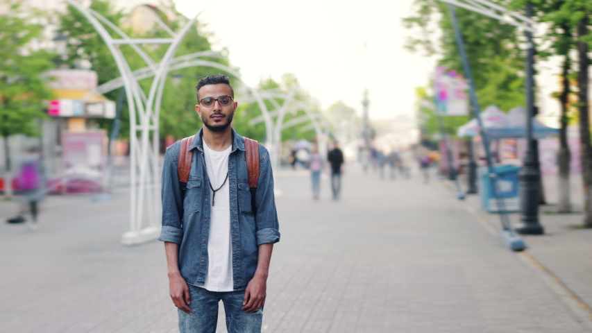 Time lapse of bearded Arab standing in the city street alone with backpack looking at camera with serious face. Modern lifestyle, people and urban life concept.
