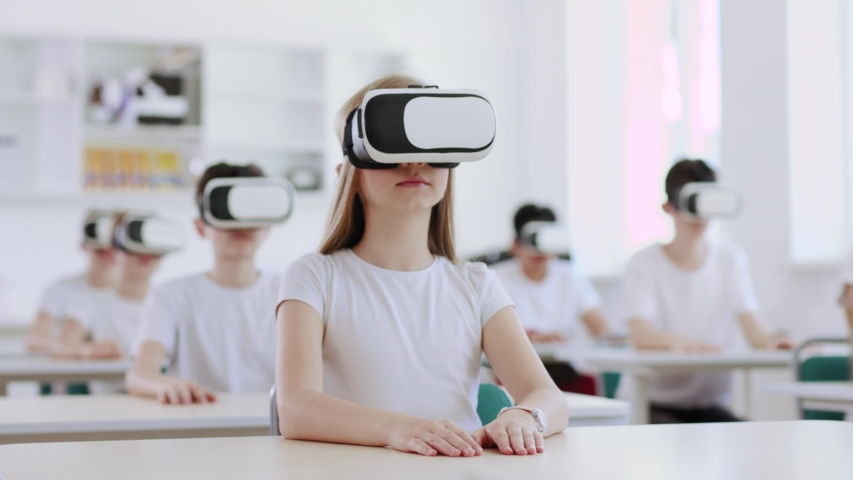 Excited preteen students using augemnted reality for studying in modern school. View of pupils with VR headsets during a computer science class.