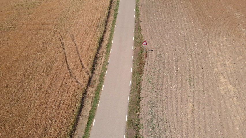 Aerial view of pilgrims walking near Santo Domingo de la Calzada, Spanish town along Camino de Santiago or Way of Saint James. Two people on road in Spain seen from drone flying in sky | Shutterstock HD Video #1032518384