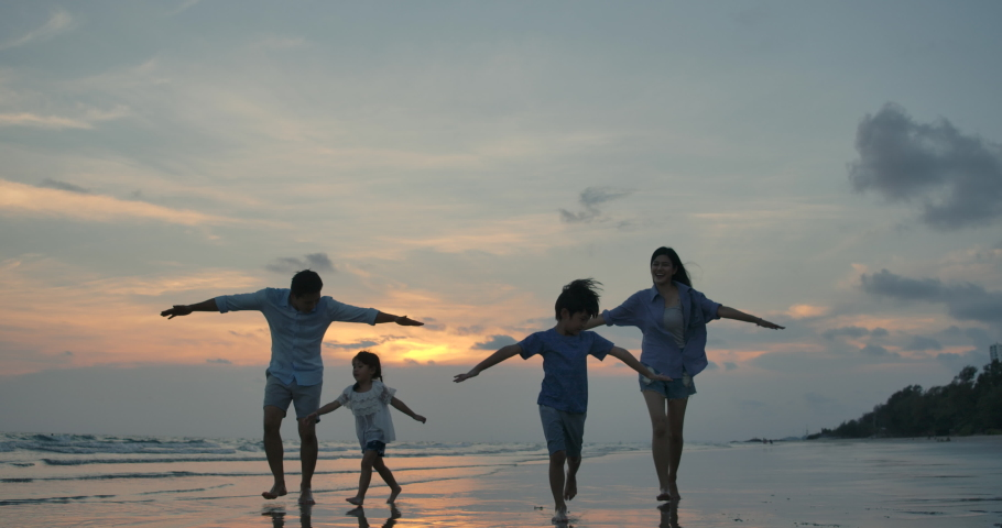 Silhouetted happy asian family playing and having fun on the beach at sunset. Slow Motion. Family, Freedom and Travel concept.  | Shutterstock HD Video #1032588314