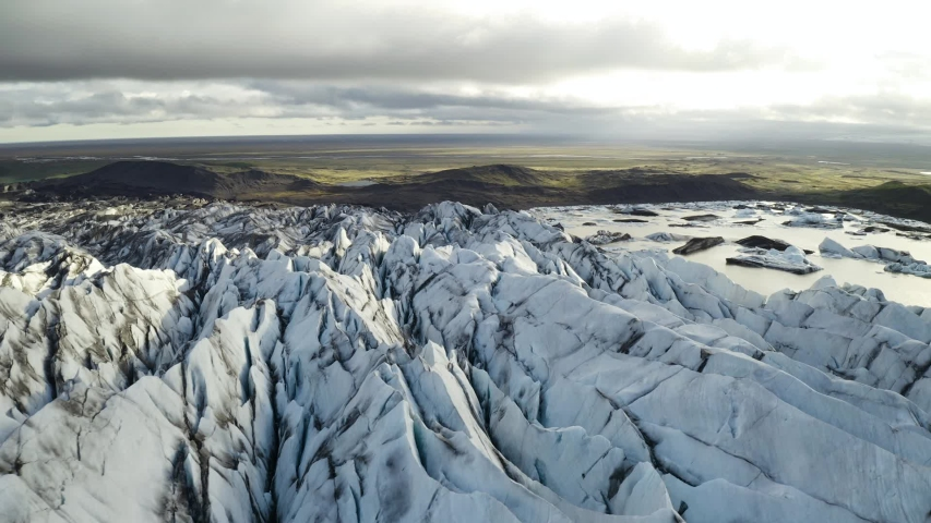 Aerial: Close up of Largest Glacier in Europe Vatnajokull Iceland Sunny day. Ridges with black ash. Melting ice. Concept of global warming   Shutterstock HD Video #1032689834