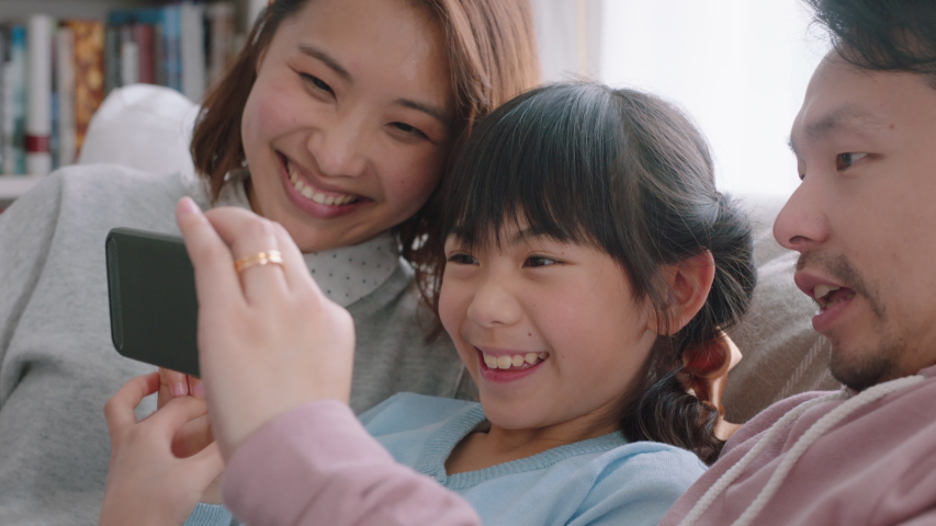 Happy asian family having video chat using smartphone at home mother and father with daughter chatting on mobile phone together waving hand enjoying online communication 4k footage