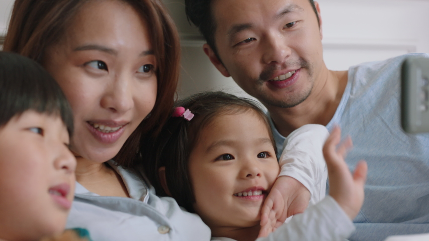 Happy asian family having video chat using smartphone in bed mother and father with children waving chatting to friends on mobile phone enjoying online communication 4k footage | Shutterstock HD Video #1032769754