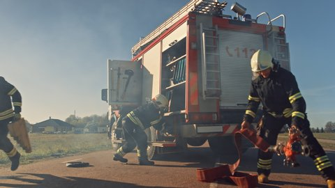 Rescue Team of Firefighters Arrive at the Crash, Catastrophe, Fire Site on their Fire Engine. Firemen Grab their Equipment, Prepare Fire Hoses and Gear from Fire Truck, Rush to Help Injured People.