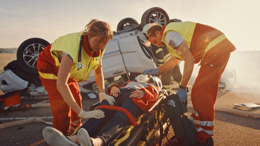 On the Car Crash Traffic Accident Scene: Paramedics Save Life of a Female Victim Lying on Stretchers. They Listen To a Heartbeat, Apply Oxygen Mask and Give First Aid. Firefighters Extinguish Fire   Shutterstock HD Video #1032836384