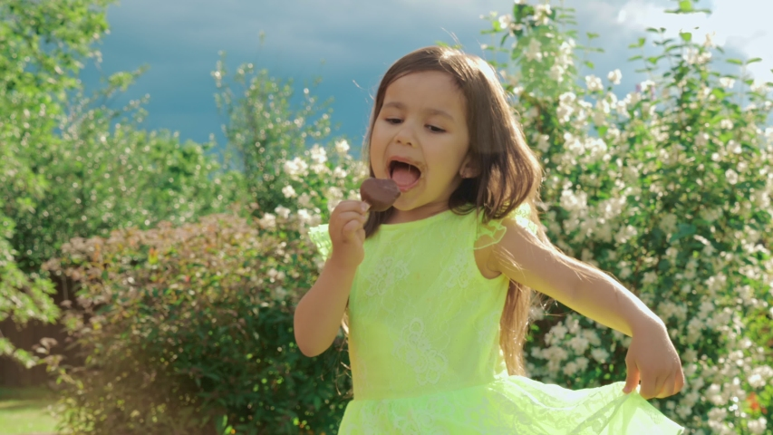 A little cute and funny girl in a bright green dress grimaces and eats chocolate ice cream. In the background is a natural public park or backyard of the house. | Shutterstock HD Video #1032947324