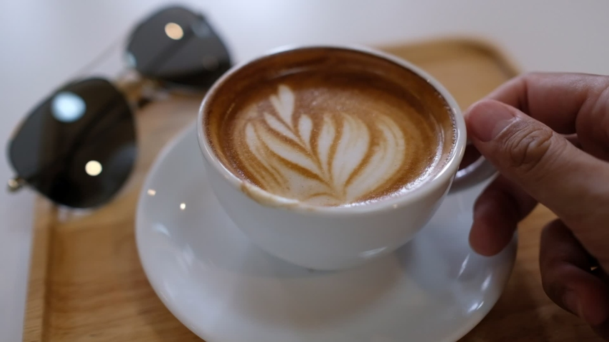 Hot latte art coffee on wood table, relax time  | Shutterstock HD Video #1032966254