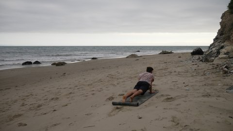 A man doing yoga poses on the beach to relax and meditate his stress away with the calming ocean waves SLOW MOTION.