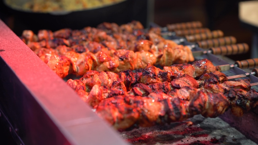 Juicy delicious barbecue is fried on hot coals on the grill. It rotates on a spit around its axis. Food festival Fried juicy meat on skewers. Pork meat is fried on coals.   Shutterstock HD Video #1033016054
