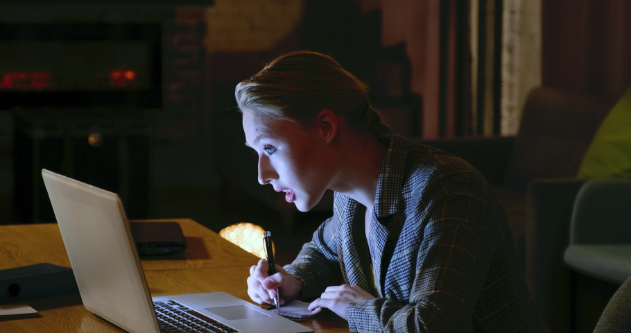 A freelancer girl works at a laptop in the evening at a large table in a large room. portrait of a working girl. 4k 10bit 422 | Shutterstock HD Video #1033018784