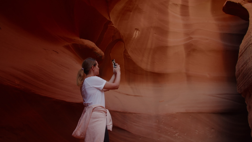 Caucasian female taking pictures with her phone in Antelope Canyon, Arizona. 4K UHD RAW edited footage | Shutterstock HD Video #1033024154