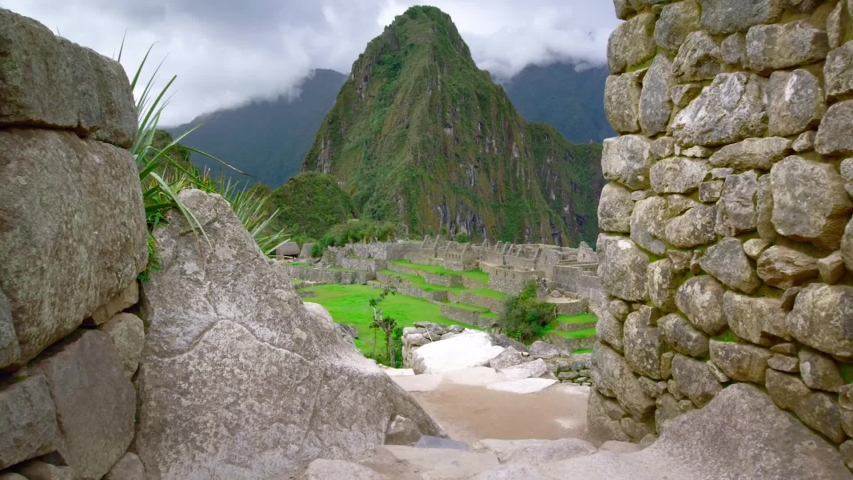 Machu Picchu Landscape reveal. Slow track past ancient stone wall to reveal misty Machu Picchu - Panning shot of the magnificent ancient citadel high in the Andes mountain range.
