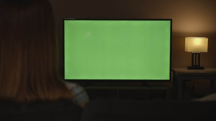 woman watching green screen tv and getting phone call in evening, 4k #1033241654