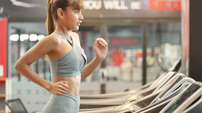 Young beautiful woman asian running on a treadmill at gym. Fitness and healthy lifestyle concept. Side view of girl in sportswear jogging exercise. real time | Shutterstock HD Video #1033243154
