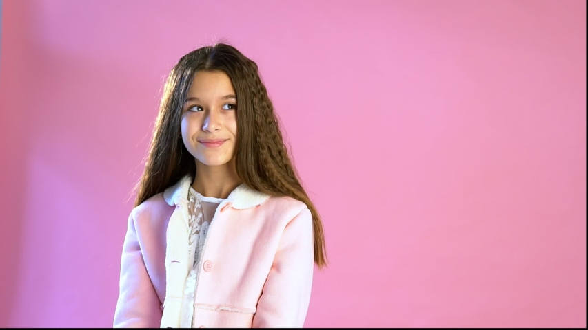 Young girl poses on a pink background | Shutterstock HD Video #1033248854