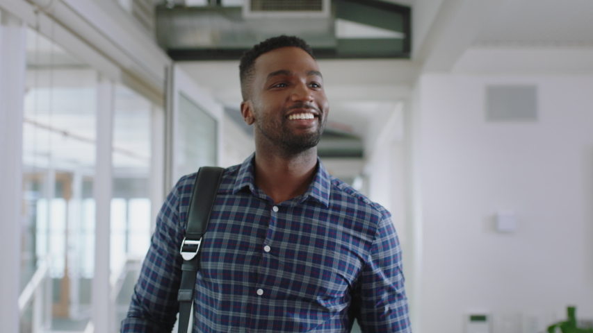 Happy african american businessman walking through office arriving at work smiling confident enjoying first day at new job 4k