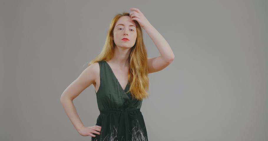 Young redhead beauty with red lipstick in beautiful dress doing hair in front of mirror getting ready for date. important event. | Shutterstock HD Video #1033258574