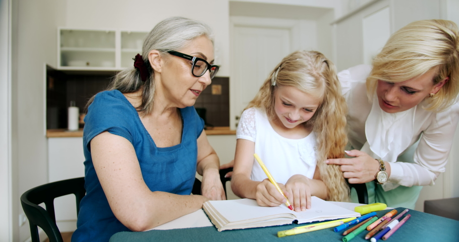 Cute blond girl drawing picture spending family time together, indoors view of appartments | Shutterstock HD Video #1033267754