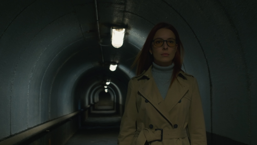 Tilt up front view shot of redhead businesswoman in a coat walking through the tunnel in the evening | Shutterstock HD Video #1033286654