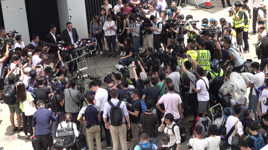 HONG KONG - 2 JULY 2019: Crowds of camera crews and reporters listen to speech of Andrew Leung, President of the Hong Kong Legislative Council, one day after the parliament was ransacked by protesters #1033365794