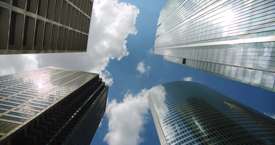 Looking up at business skyscrapers buildings in dowmtown, clouds rolling in sky and reflections on glass. 4k | Shutterstock HD Video #1033366604