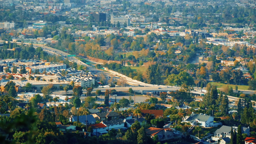 View of the city with green spaces. Green mountains in the city with a lot of beautiful trees. Freeway aerial view. Breathtaking look at busy city from the hills. Timelapse overlook.