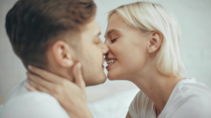Beautiful woman embracing and kissing smiling man at home | Shutterstock HD Video #1033412924