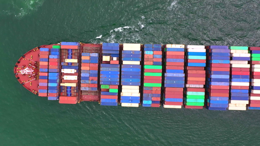 Top aerial view of the large volume of containers on ship sailing in the sea carriage the shipment from loading port to destination discharging port, transport and logistics services to worldwide  | Shutterstock HD Video #1033527494