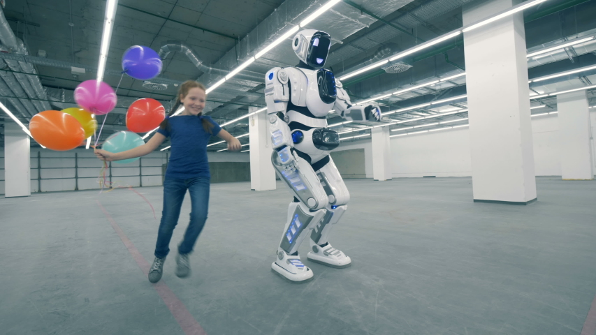 Happy girl playing with a robot, close up. | Shutterstock HD Video #1033569764