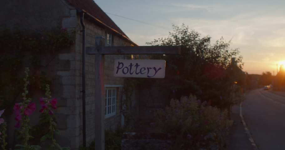 A beautiful street view of a small village at sunset with a pottery sign. HANDHELD DOLLY SHOT.   Shutterstock HD Video #1033615004