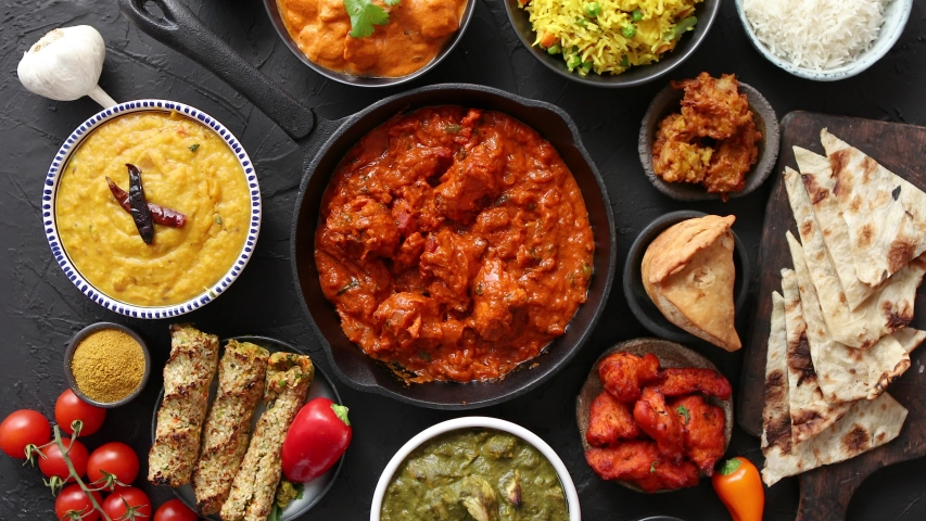 Assortment of various kinds of Indian cousine on dark rusty table. Chicken Tikka Masala, Butter, Nilgiri, Daal Tarka. Served with fried rice, naan bread and spices.   Shutterstock HD Video #1033649384