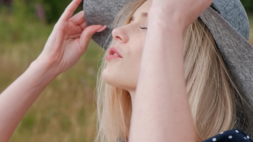 A young attractive blond woman in a blue dress and hat is sitting on a plaid on the grass. The wind blows hair. Picnic in nature. | Shutterstock HD Video #1033706114
