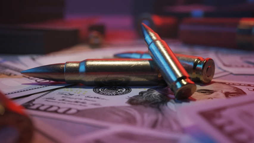 Shiny, brand new ammo bullets in the middle of mafia table. A lot of dollar bills stacked on top of it  Gangster crime wealth and deadly force. Neon red and blue lights illuminating the cash. 4KHD  | Shutterstock HD Video #1033790774