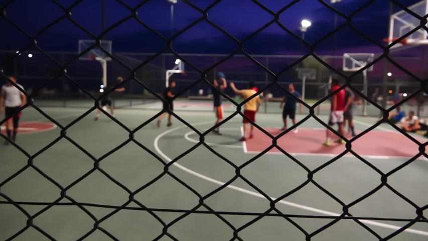 The Basketball At Night stock video is a great piece of video that contains men playing basketball outdoors on a court fenced in with wires.  | Shutterstock HD Video #1033842164