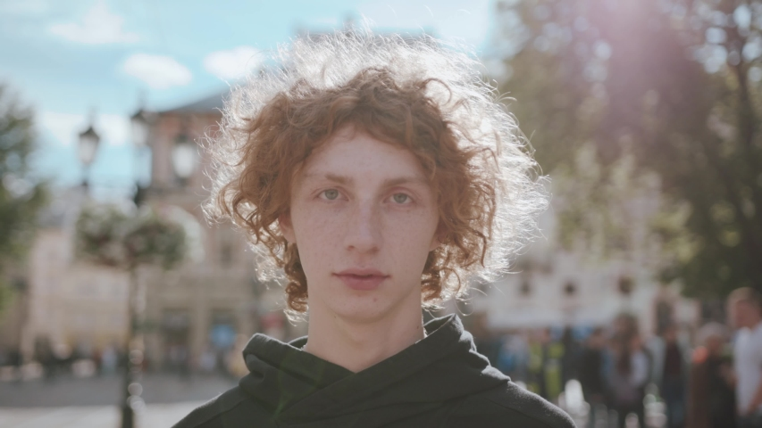 Smiling cheerful boy curly hair standing on the street look at camera handsome male stylish urban young lifestyle outside person , beautiful cool model outdoors hipster slow motion | Shutterstock HD Video #1033865684