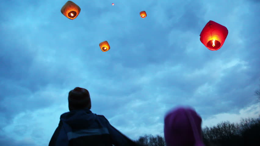 Boy And Girl Look Up To Glowing Chinese Lanternes In Sky Among Clouds Stock Footage Video 1033939