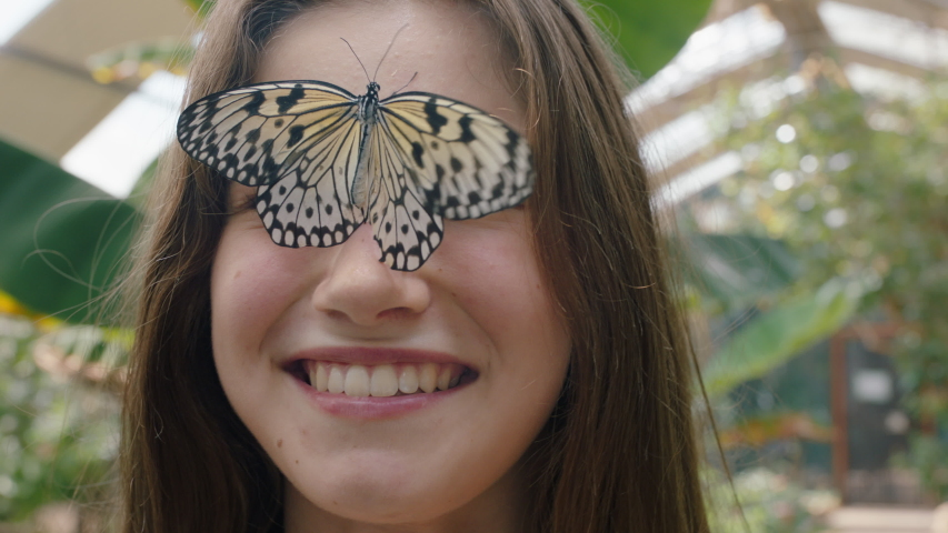 Beautiful girl smiling with butterfly on face fluttering wings having fun with wildlife in nature conservation zoo 4k | Shutterstock HD Video #1034054084
