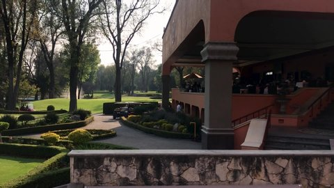 Lopez mateos, state of mexico / mexico - 04 17 2019: february 21 2019,  state of mexico, mexico: view of an elegant restaurant and beautiful golf  course on a typical hacienda in slow motion